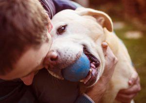 Man hugging dog reward for fetching