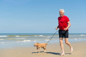 running with dog at beach | Ultimate Pet Nutrition